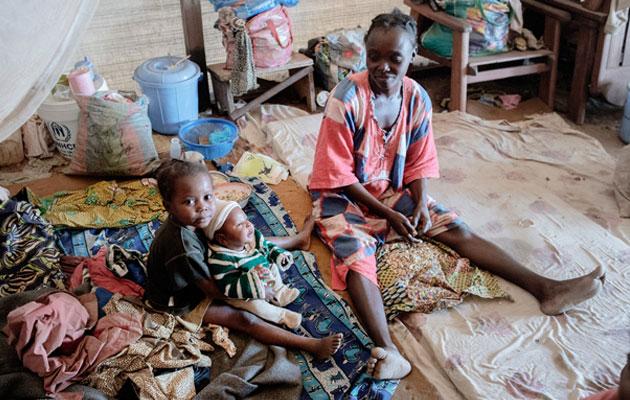 Nadège sidder med to af sine børn. Hun flygtede under konflikten i Den Centralafrikanske Republik. Hendes børn lider af sygdomme som malaria, men vi giver børnene lægehjælp.