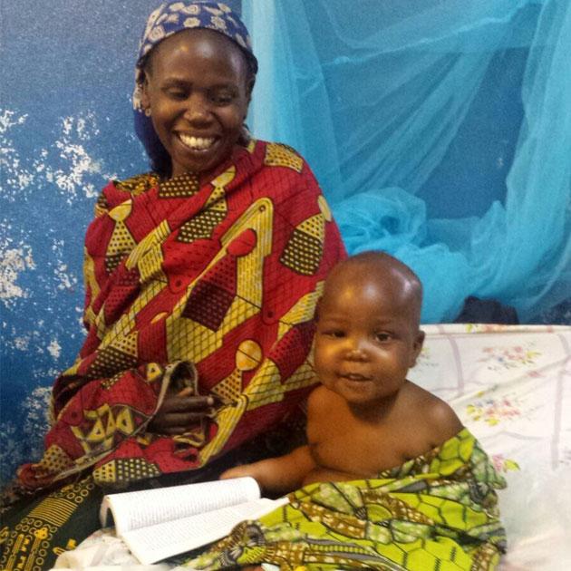 Smilet er tilbage hos drengen Mukiza og hans mor efter behandlingen for fejlernæring.