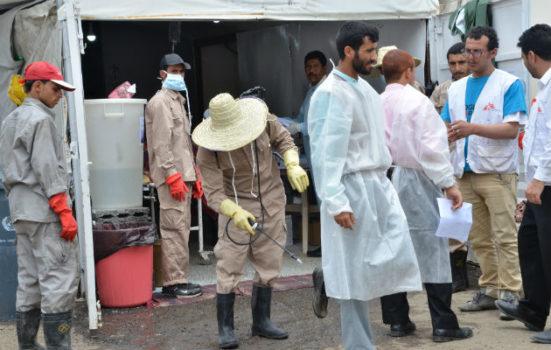 Vagtskifte. En sygeplejerske er lige kommet ud af et af vores kolerabehandlingscentre i Yemen. En medarbejder er i færd med at desinficere hans sko med en klorinholdig væske for at undgå smittespredning.
